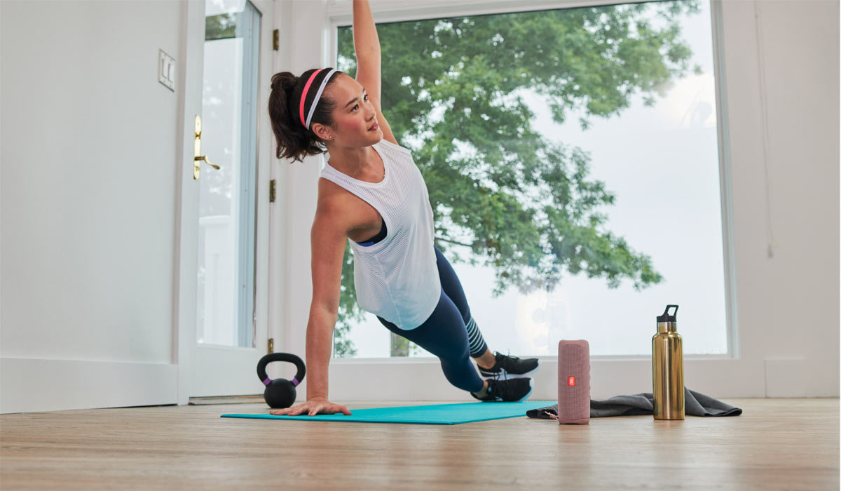 A woman exercises at home with a JBL speaker