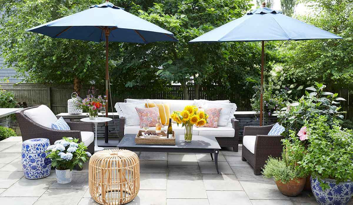 Patio with rattan furniture, plants, and two umbrellas photo