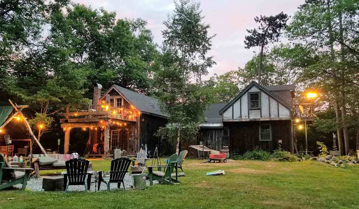 A backyard with firepit, adirondack chairs, and lights