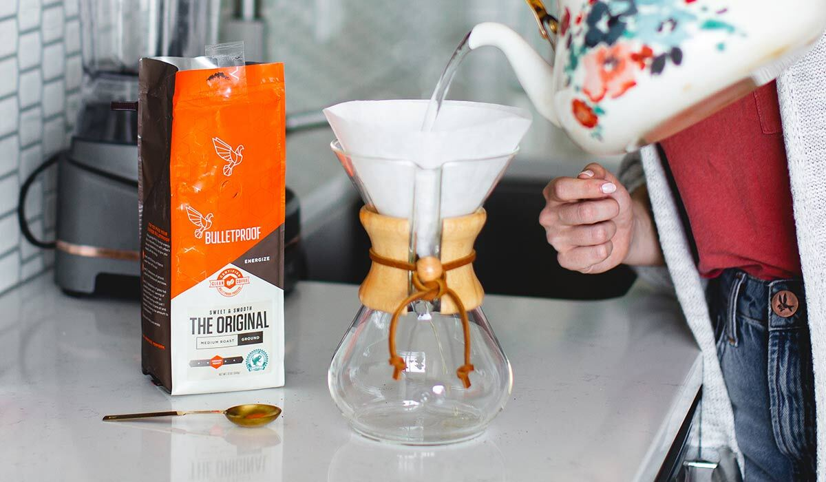 A woman pours Bulletproof coffee in a Chemex