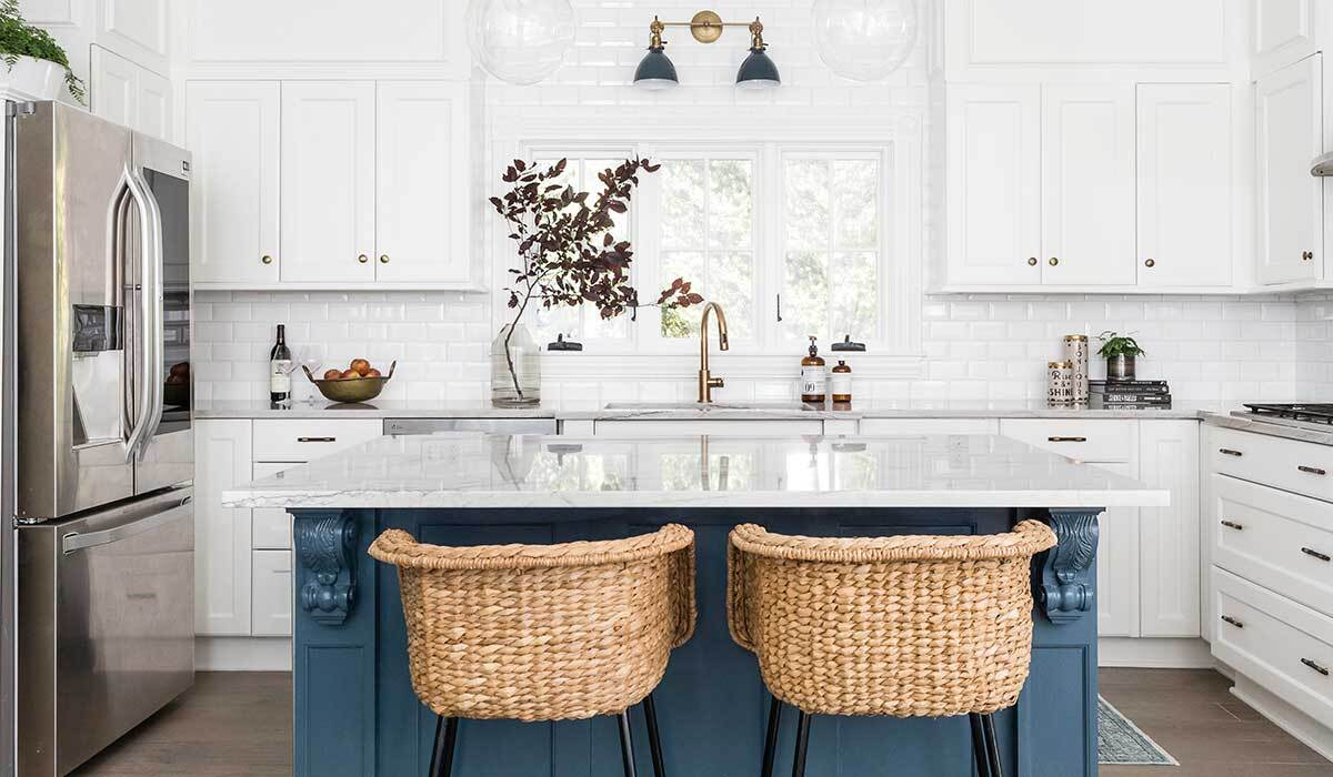 White kitchen with blue island and rattan barstools