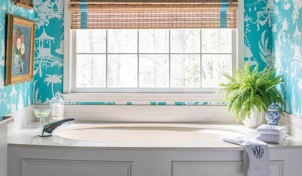 Bathroom with blue printed wallpaper and bamboo window shade photo