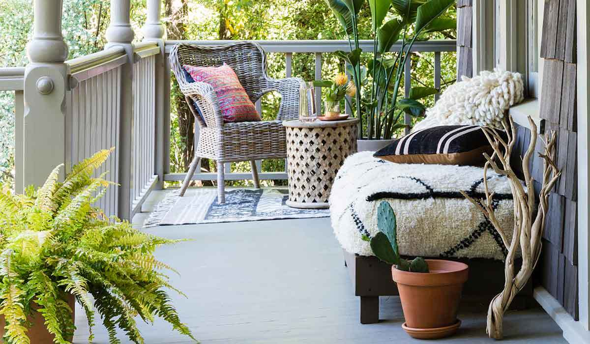 Eclectic porch with rattan chair and upholstered bench photo