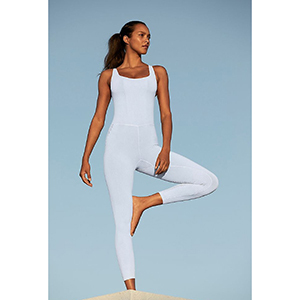 A woman wears a white good karma onesie from FP Movement photo