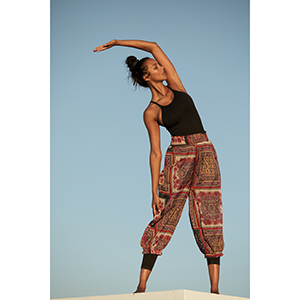 A woman stretches while wearing a happiness runs FP Movement bodysuit with pants over top photo