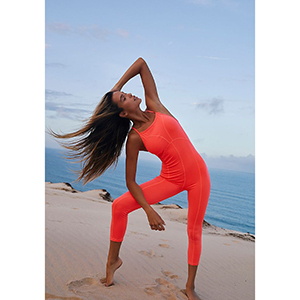 A woman wears a bright orange racerback side to side performance onesie from FP Movement photo