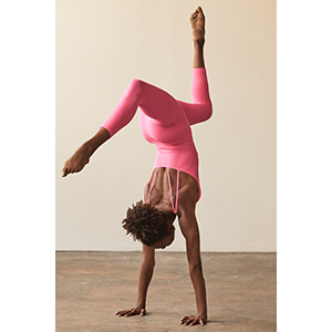 A woman does yoga in a strappy pink astro onesie from FP Movement photo