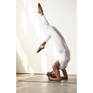 A woman does a handstand in a white perforated lovers onesie from FP Movement photo