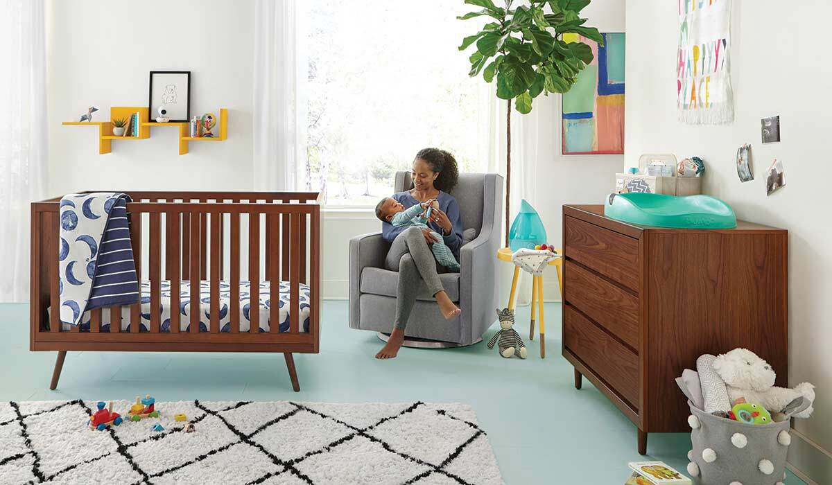 A woman feeds her baby in the nursery