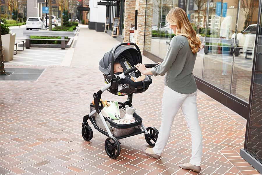 A woman uses the Graco Modes Nest stroller for her baby while on a walk