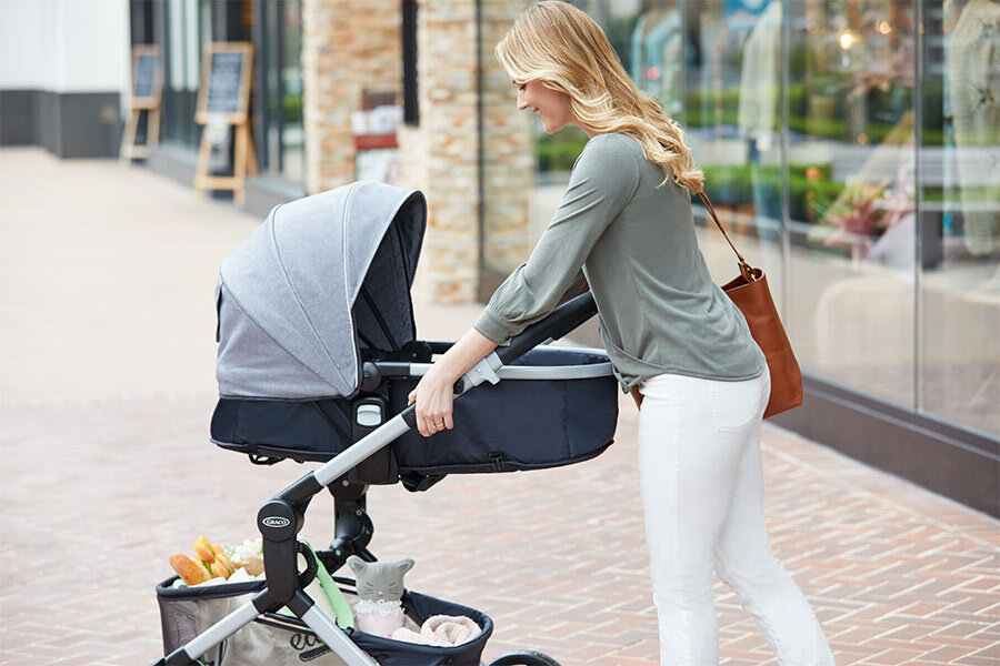A woman uses the Graco Modes Nest stroller for her baby while on a walk photo