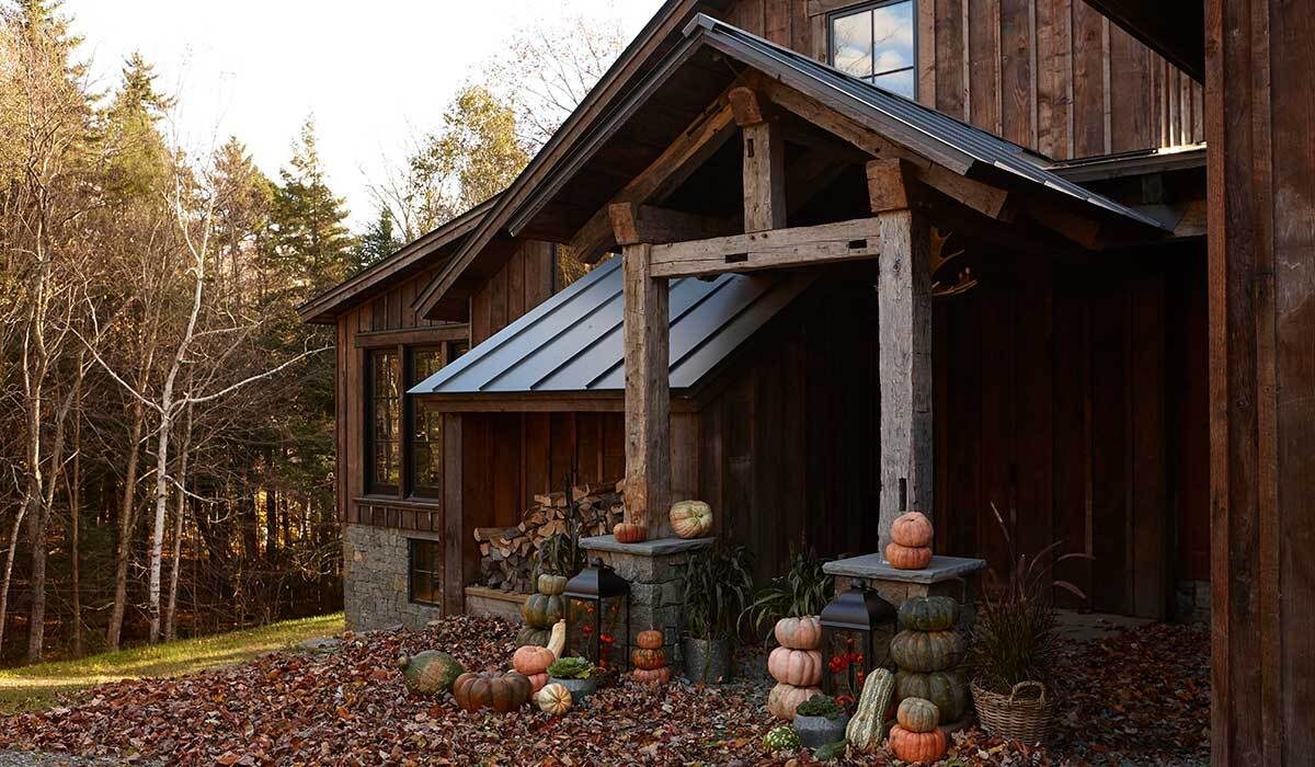 Rustic home in the woods with pumpkins surrounding the entryway