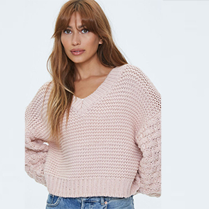 A woman wears a light pink v-neck sweater from Forever 21 photo