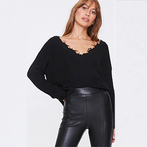 A woman wears a black distressed sweater from Forever 21 photo