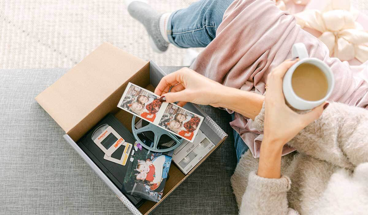 A woman looks at the photos in her Legacybox kit photo