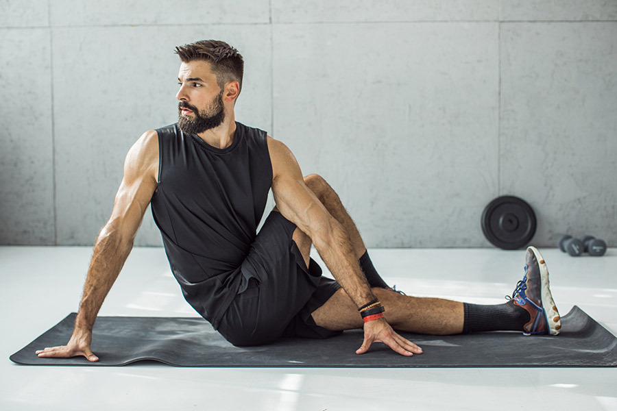 A man stretches in a gym