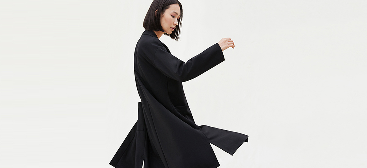 A woman wears Eileen Fisher clothes in front of a neutral background