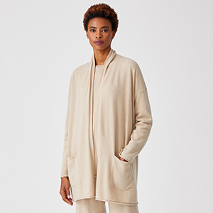 A woman wears a cream-colored cashmere cardigan from Eileen Fisher photo