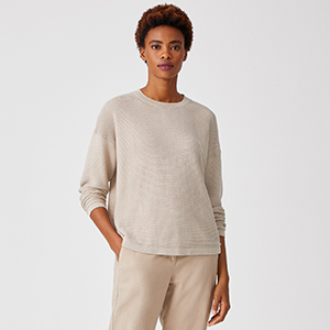 A woman wears a beige cashmere sweater from Eileen Fisher photo