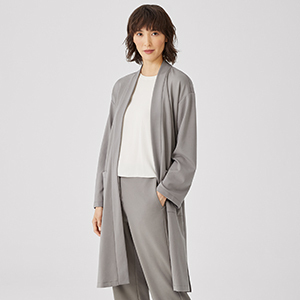 A woman wears a gray jacket from Eileen Fisher photo