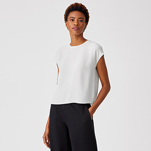 A woman wears a white short-sleeve shirt from Eileen Fisher photo