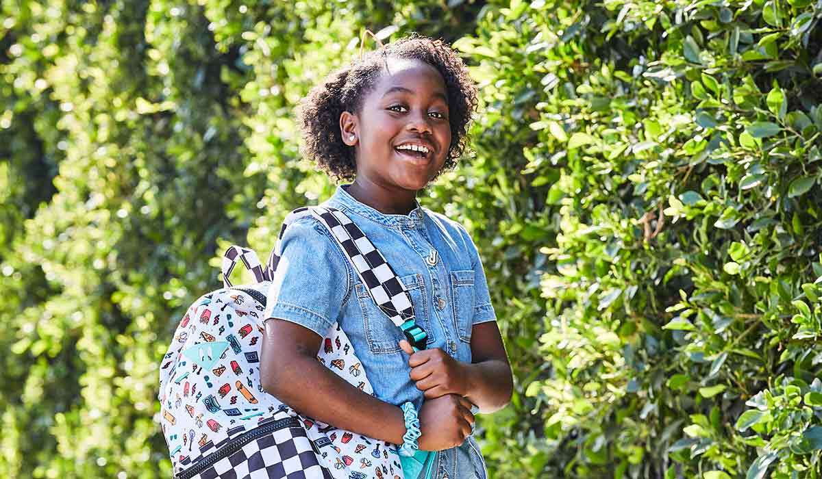 A girl smiles while wearing a backpack
