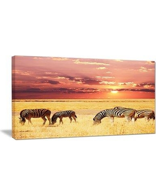 """Design Art Zebras Grazing Together at Sunset Photographic Print on Wrapped Canvas, Canvas & Fabric in Red/Brown/Yellow, Size 16"""" H x 32"""" W x 1"""" D"""