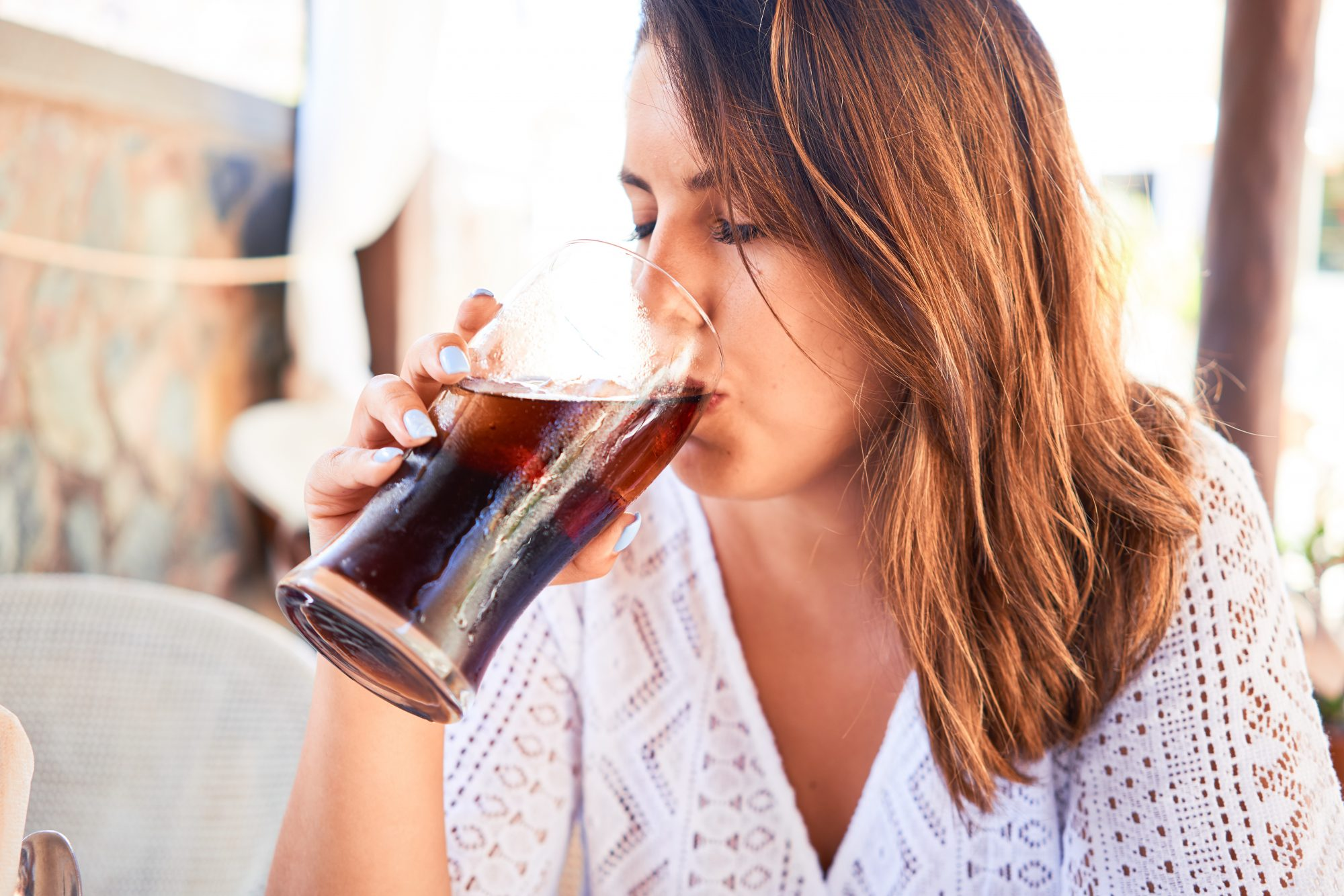 Young beautiful woman sitting at restaurant enjoying summer vacation drinking soda