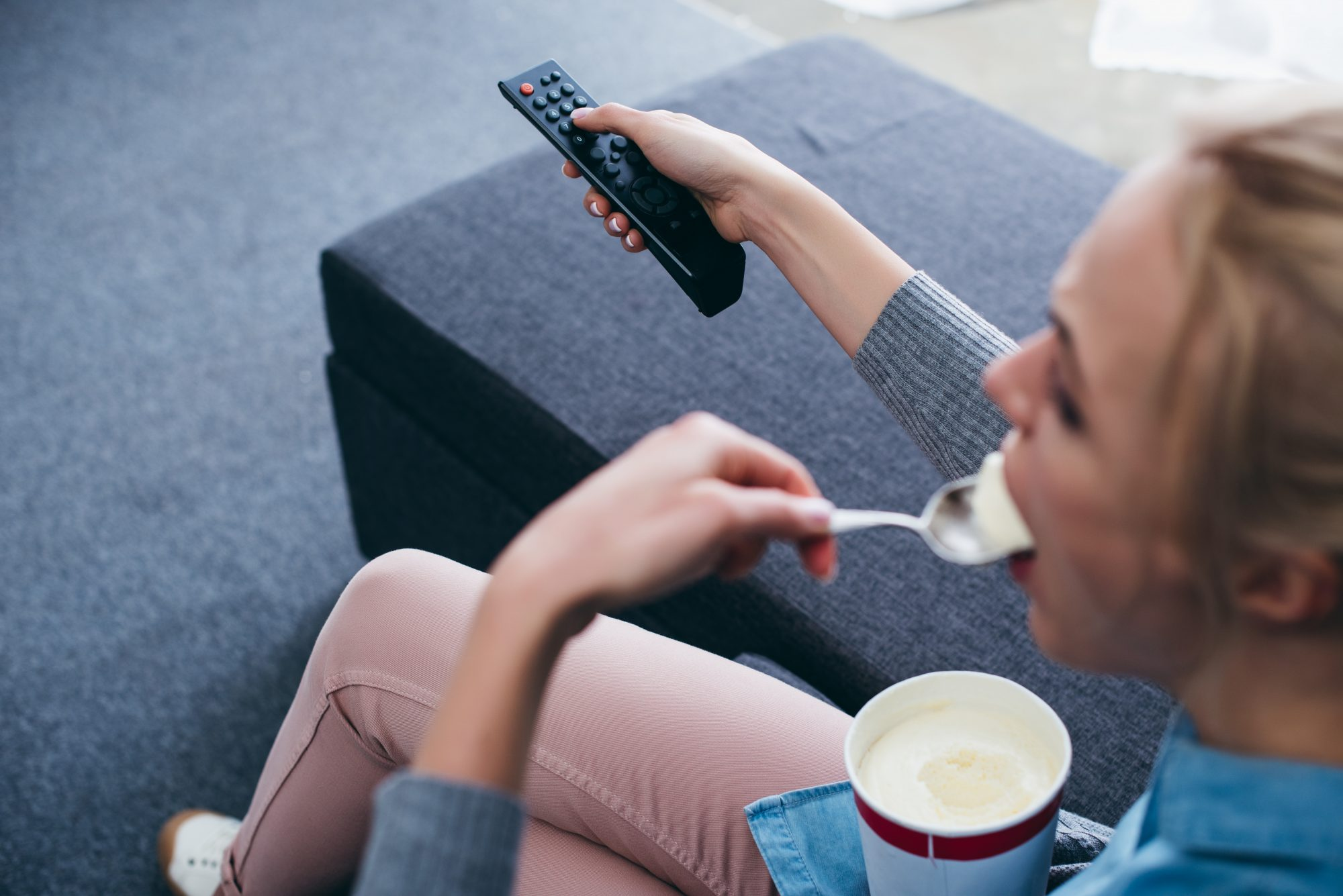 cropped view of woman sitting on couch and eating ice cream while watching tv