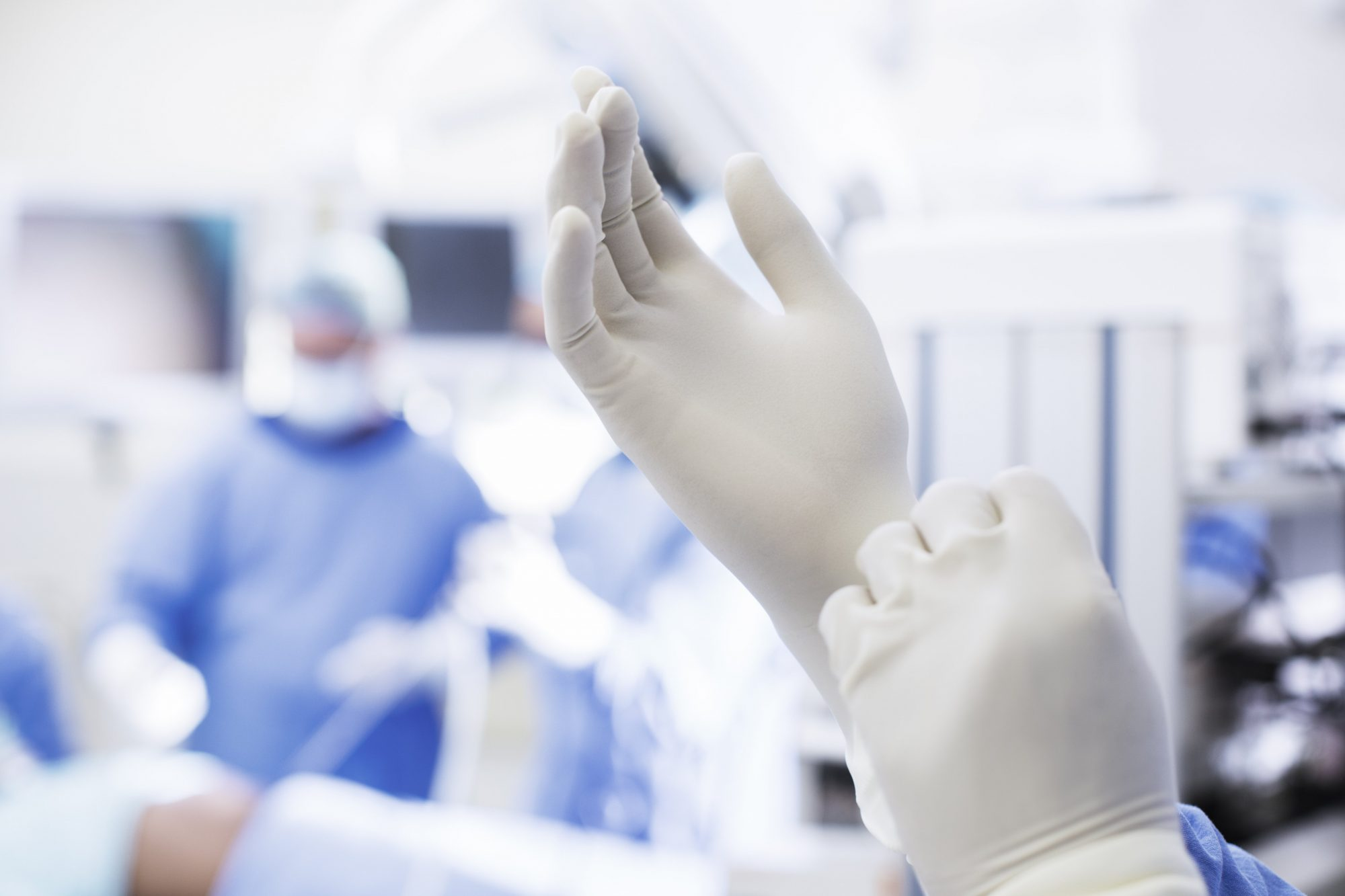 Close-up of surgeon putting on surgical gloves in operating theater