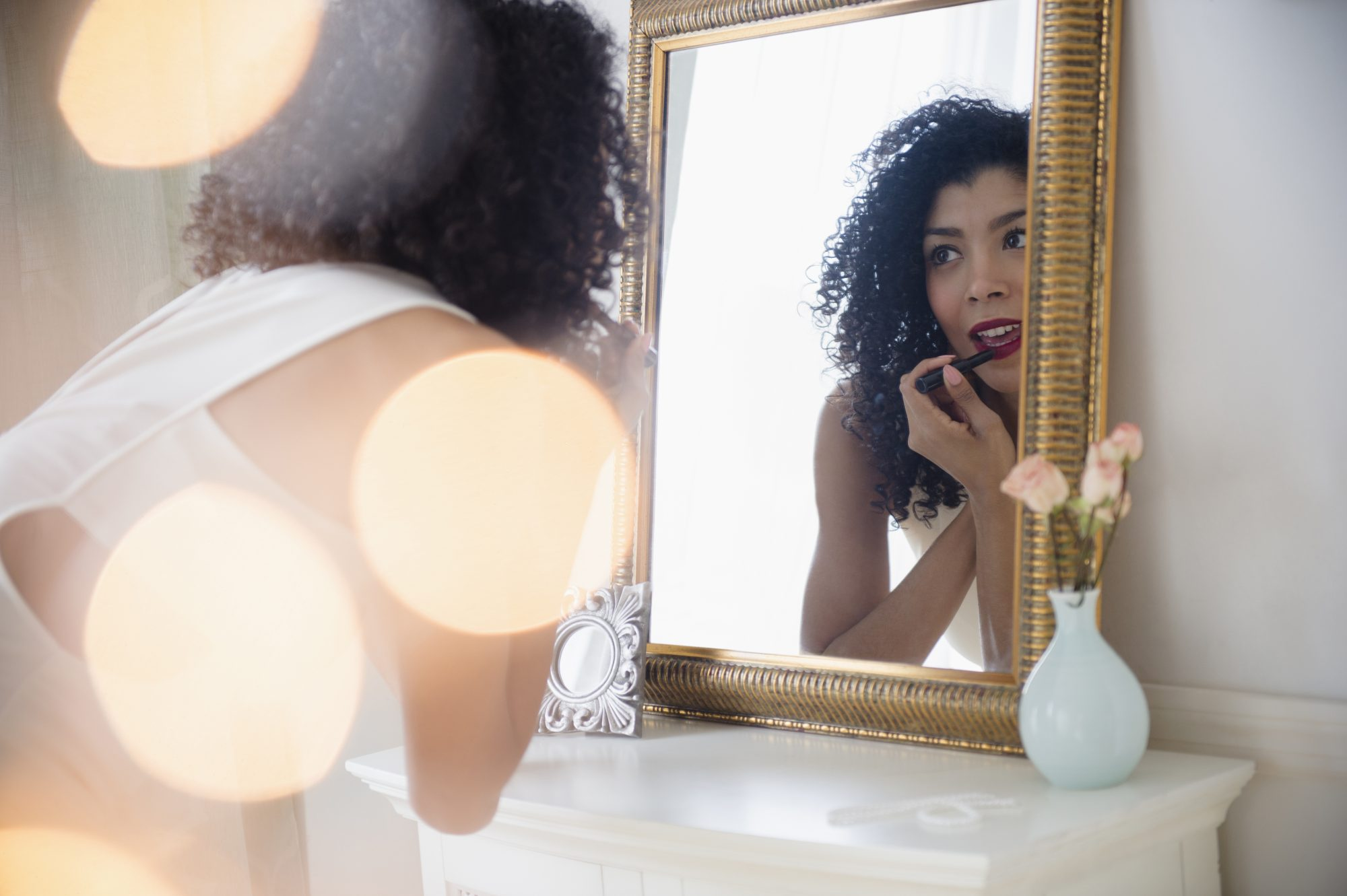 Woman applying lipstick looking in the mirror