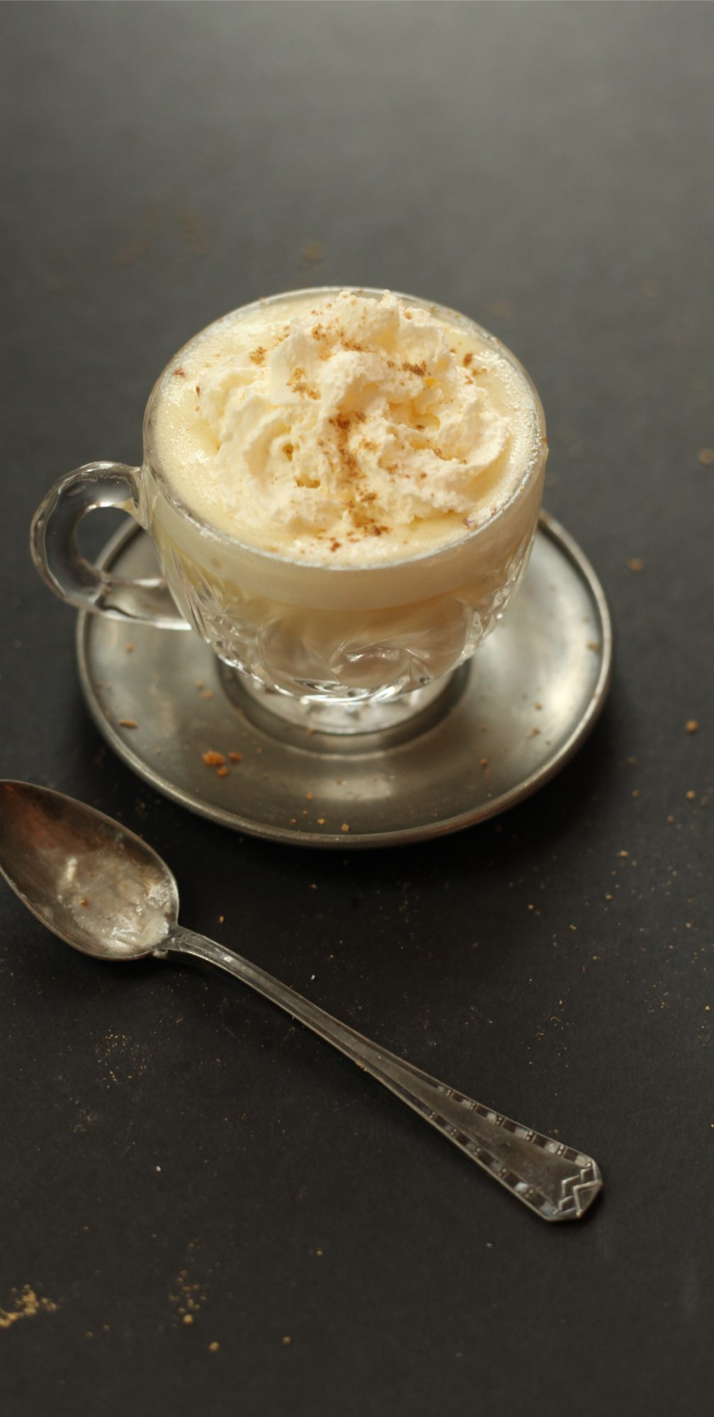 Cup of white hot chocolate with teaspoon and cream