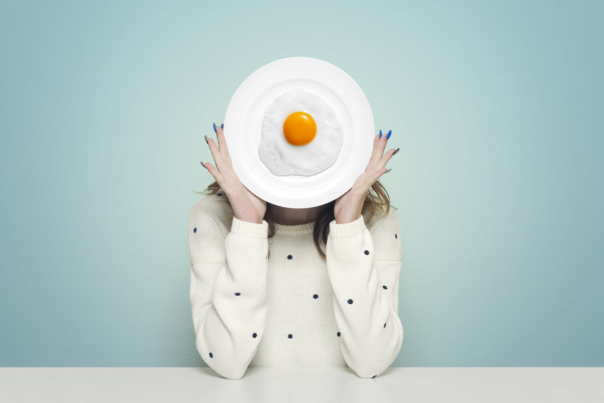 Woman hiding face with food plate egg