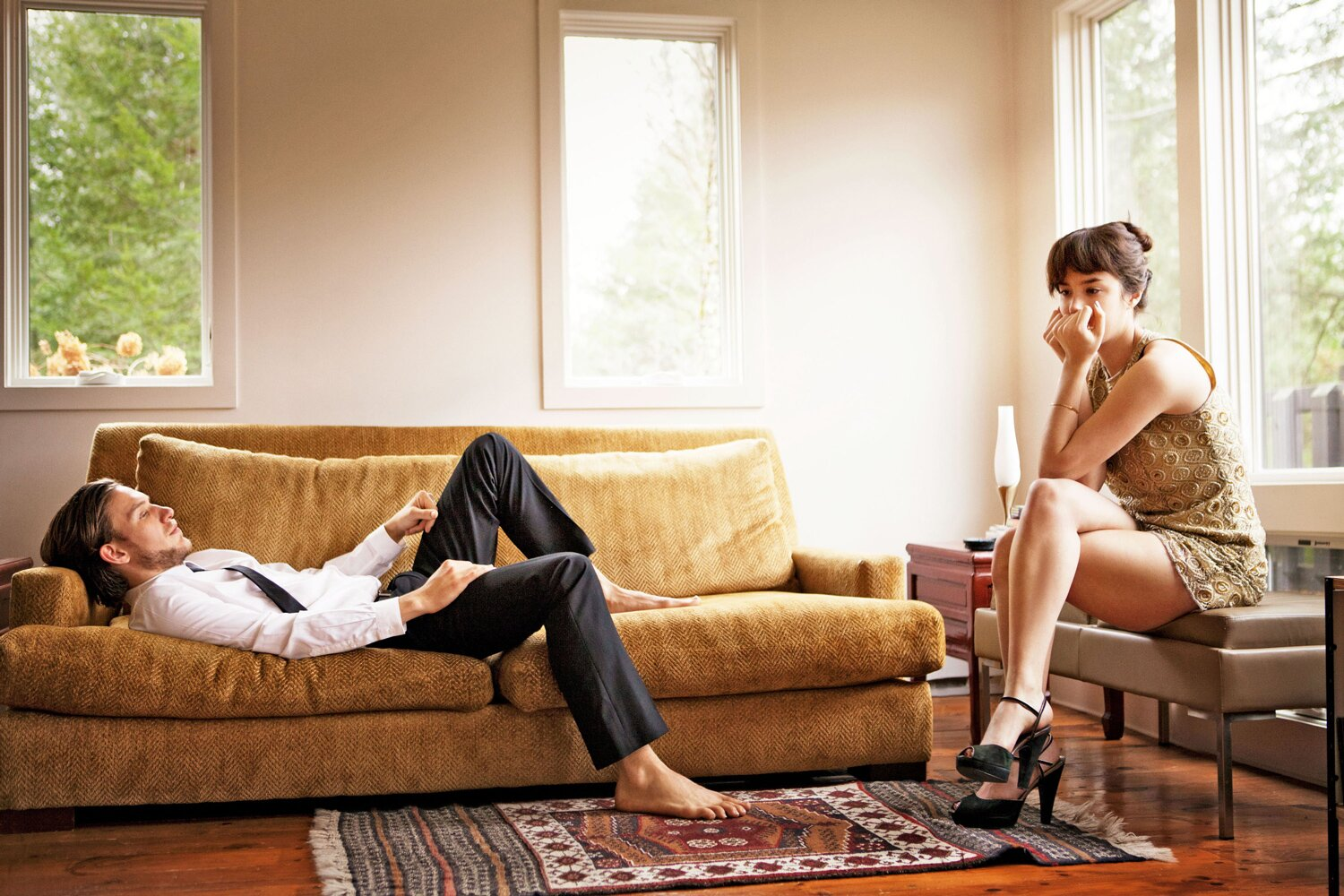 upset couple man lying on couch woman on bench