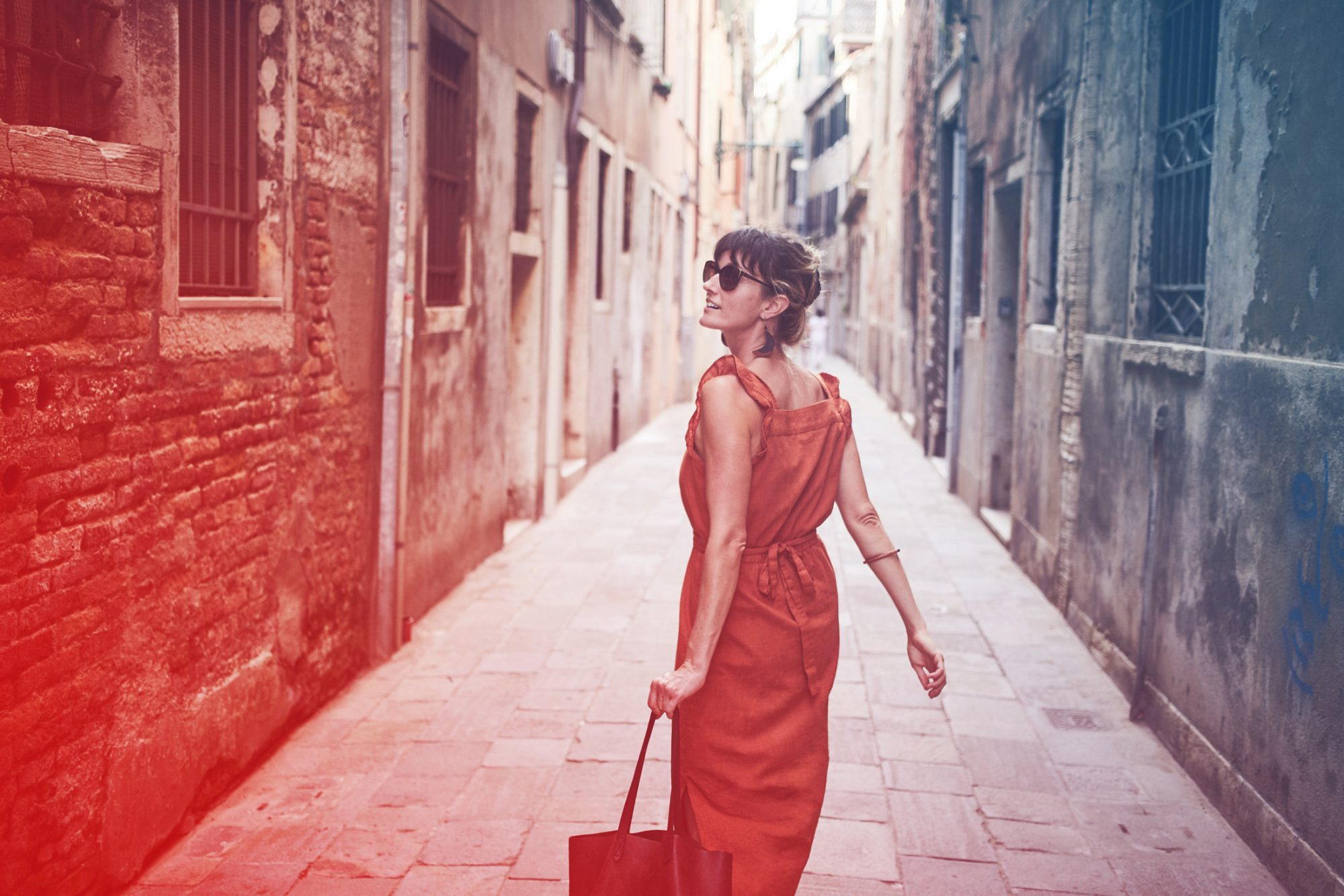 A young woman walks down an old street in Italy
