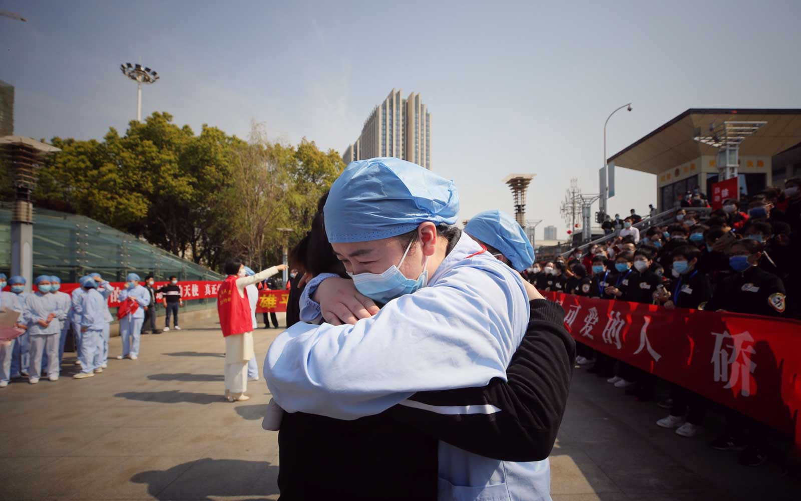 A medical worker (R) embraces a member of a medical assistance team from Jiangsu province at a ceremony marking their departure after helping with the COVID-19 coronavirus recovery effort, in Wuhan, in China's central Hubei province on March 19, 2020.