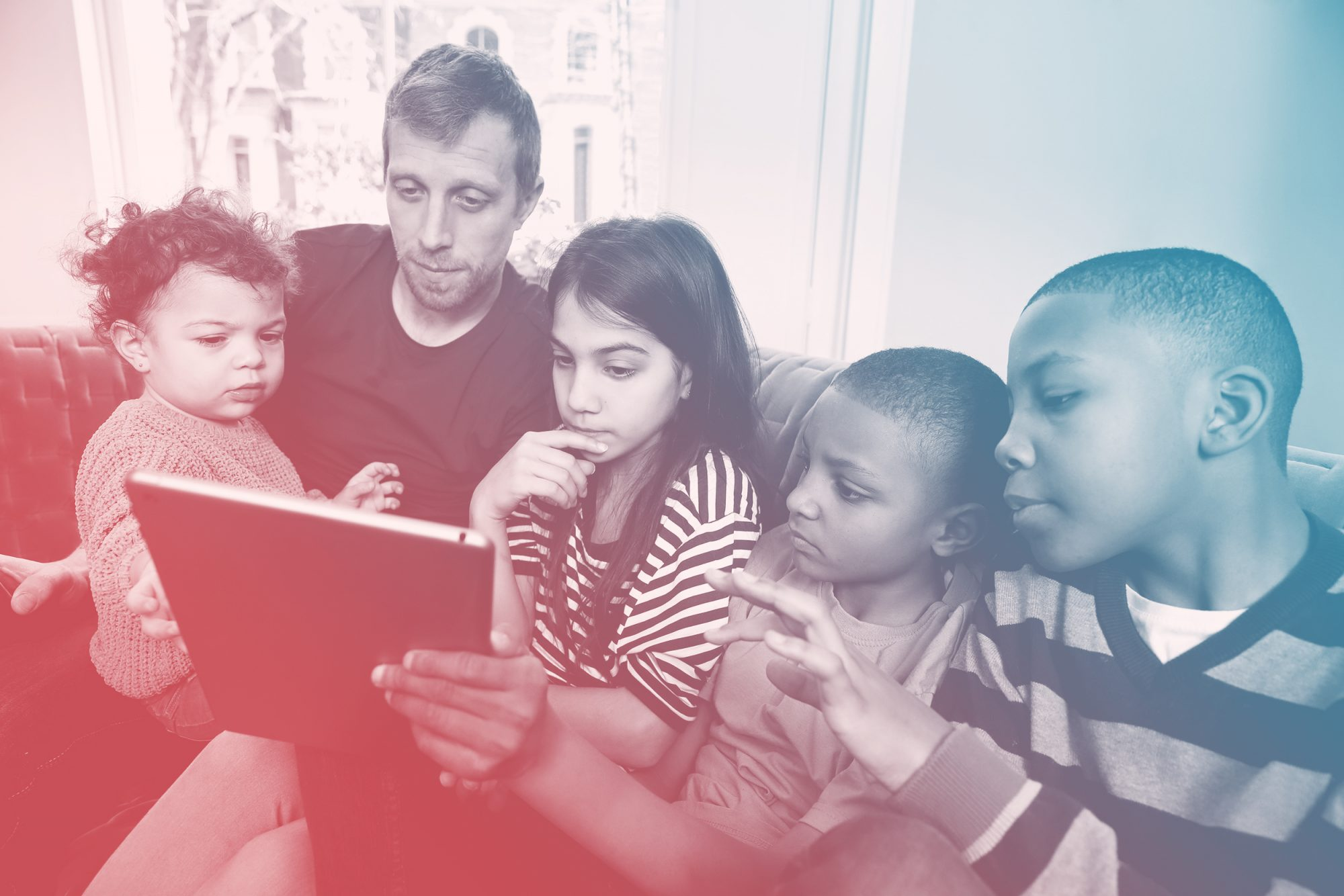 Single father with four children looking at digital tablet -Blended family using digital device on a sofa and concentrating