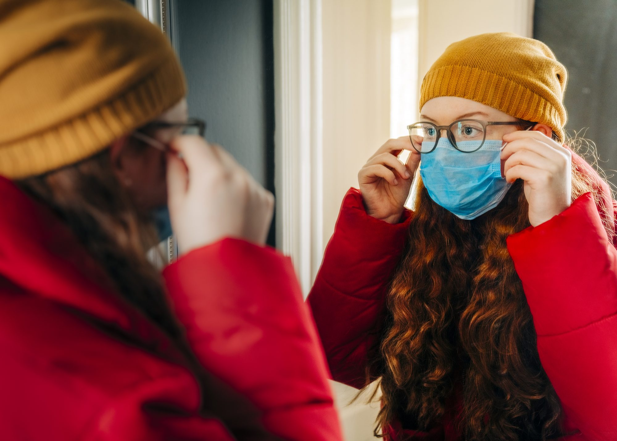 Teenage girl preparing for school wearing protective mask