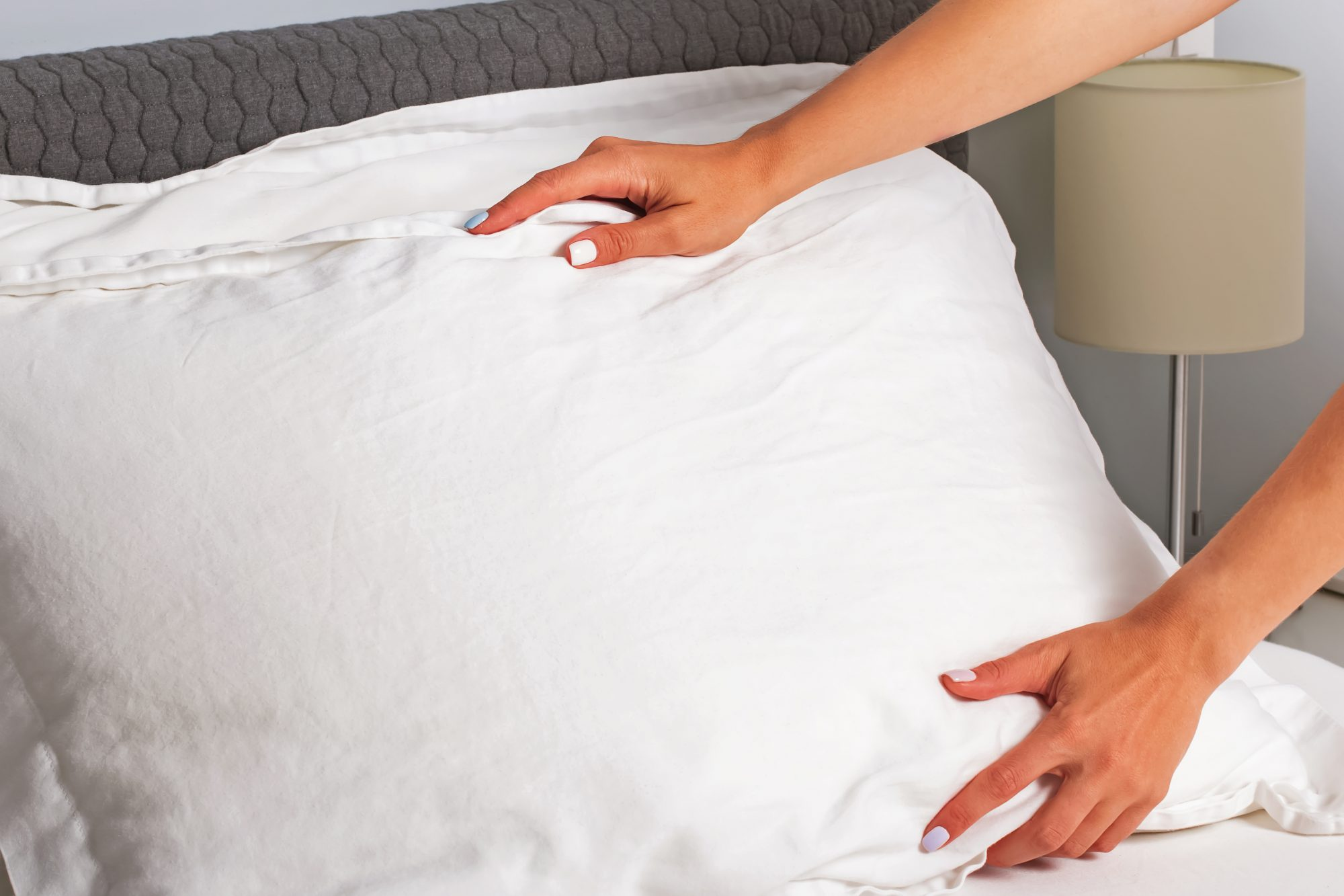 Housekeeper changing the linen and putting pillows on the bed with fresh clean white bedding. change-pillow