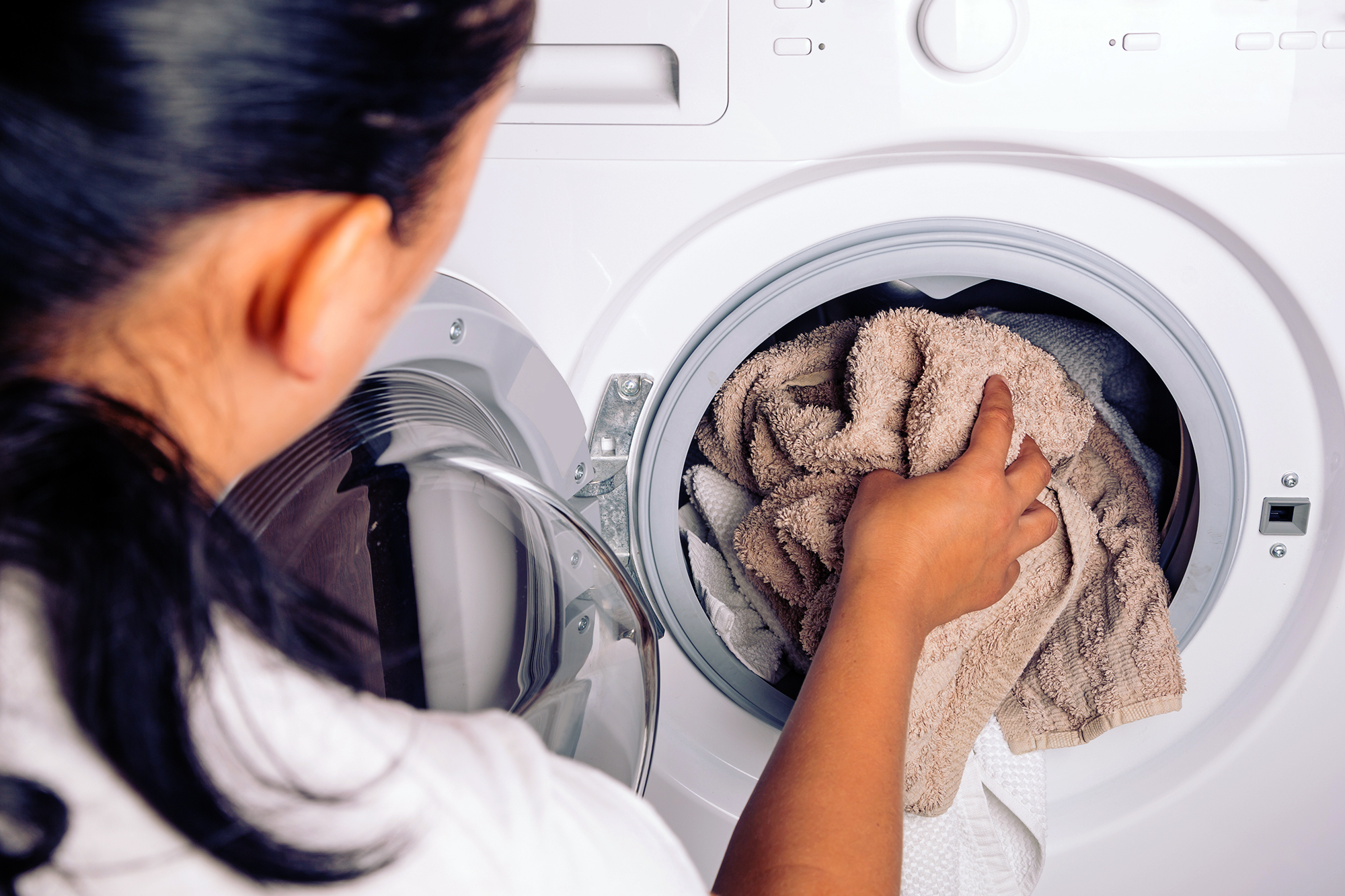 Woman loading laundry to the washing machine. laundry-stripping