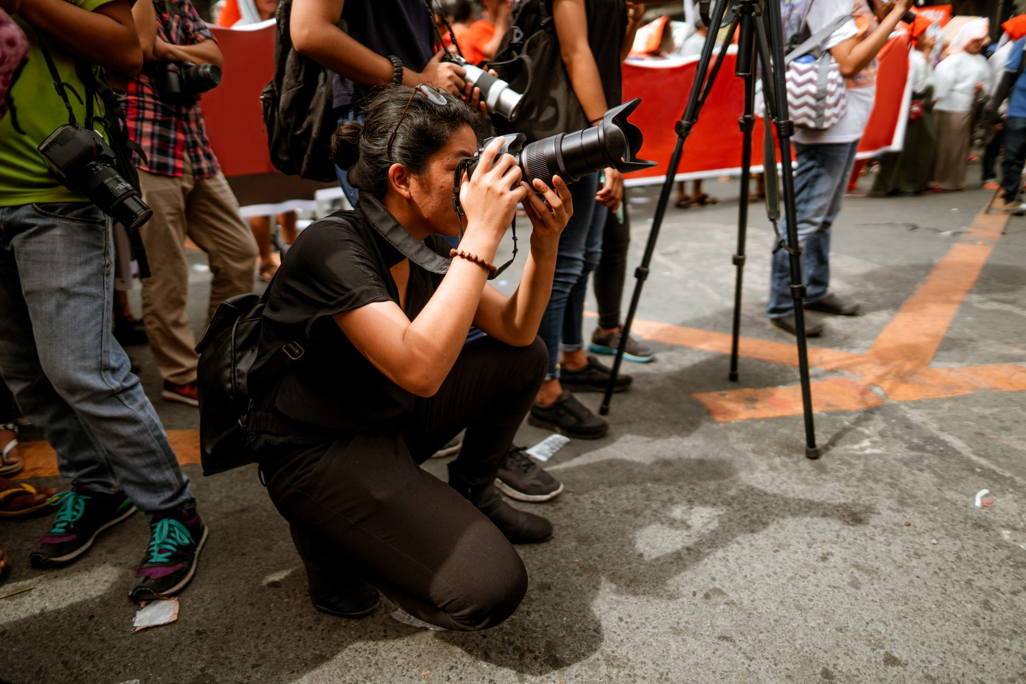 Young Filipino student photojournalist taking photographs