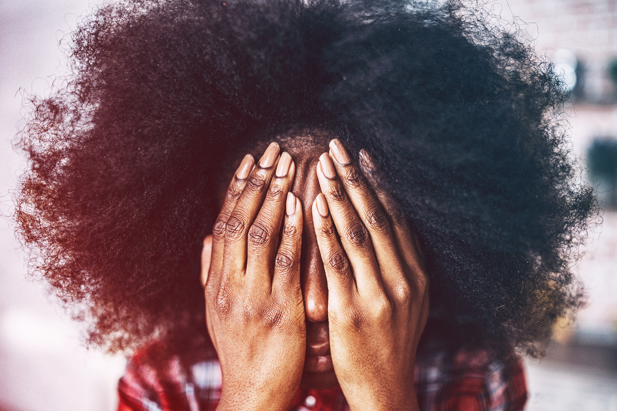 African woman sitting at home hands on face
