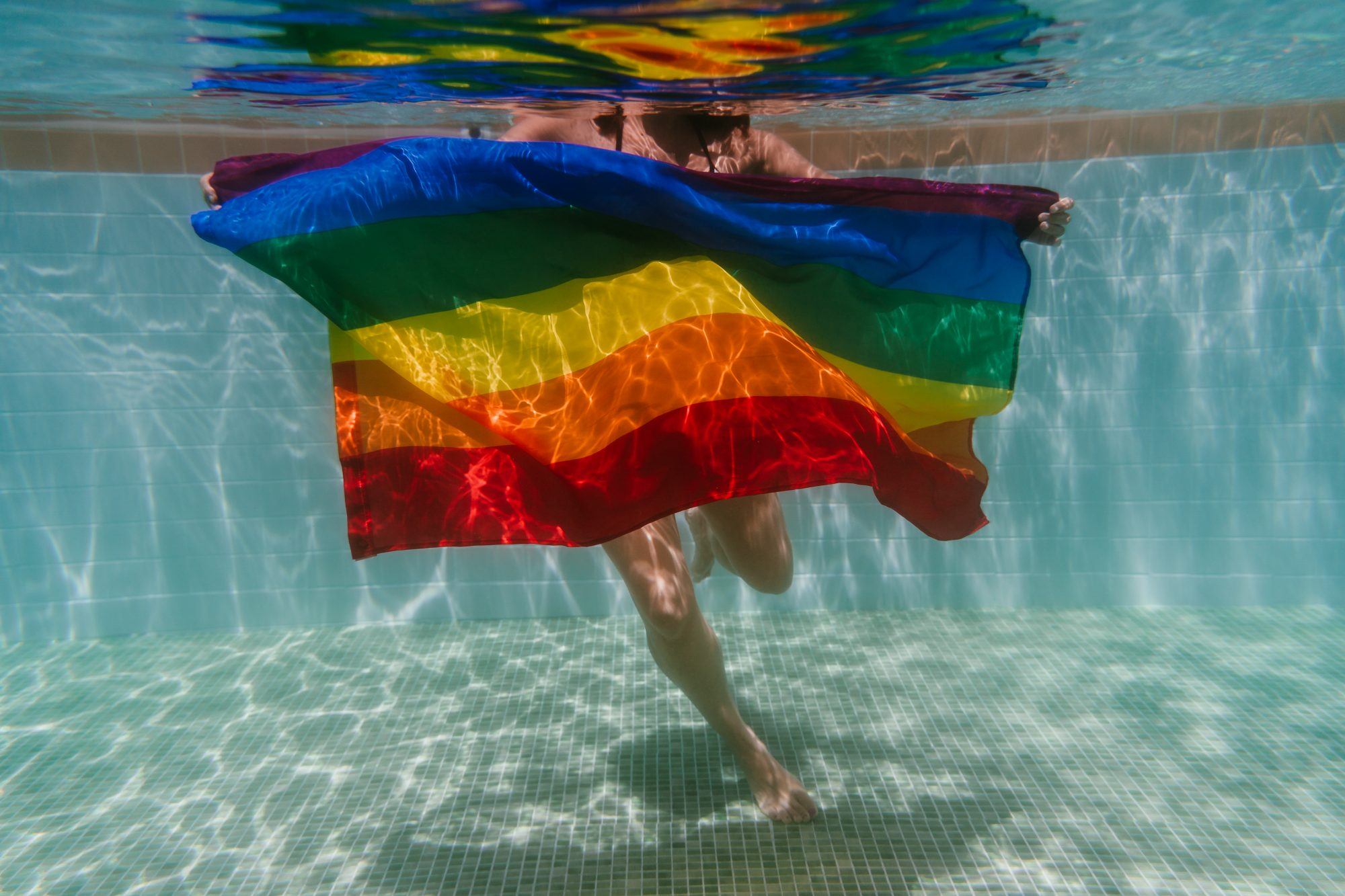 internalized-homophobia , young woman in a pool holding rainbow gay flag underwater.LGBTQ concept. Summertime