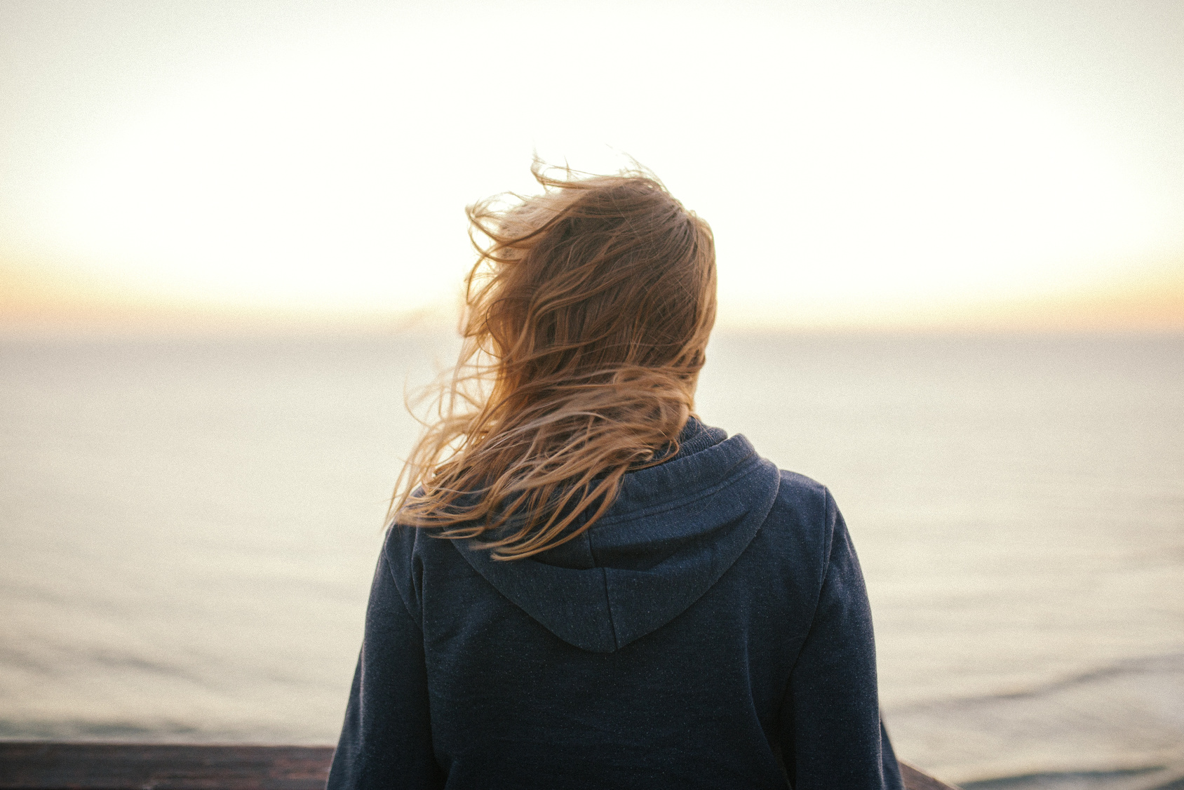 suicidal-ideation , An anonymous blond woman standing in the wind looking at the sea or ocean