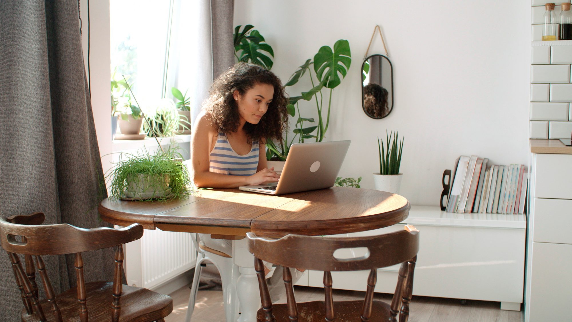 Amazon's Big Summer Sale , Charming young woman typing on laptop computer at home.