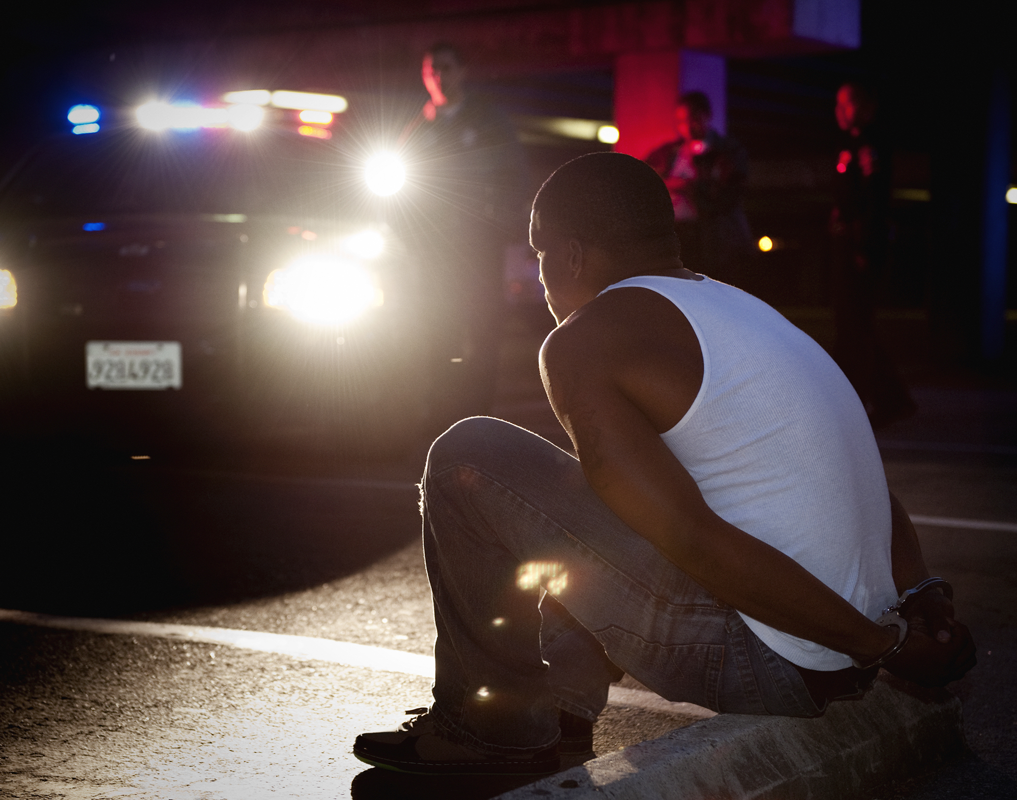 Police shining lights on handcuffed African man sitting on curb , excited delirium black man police custody