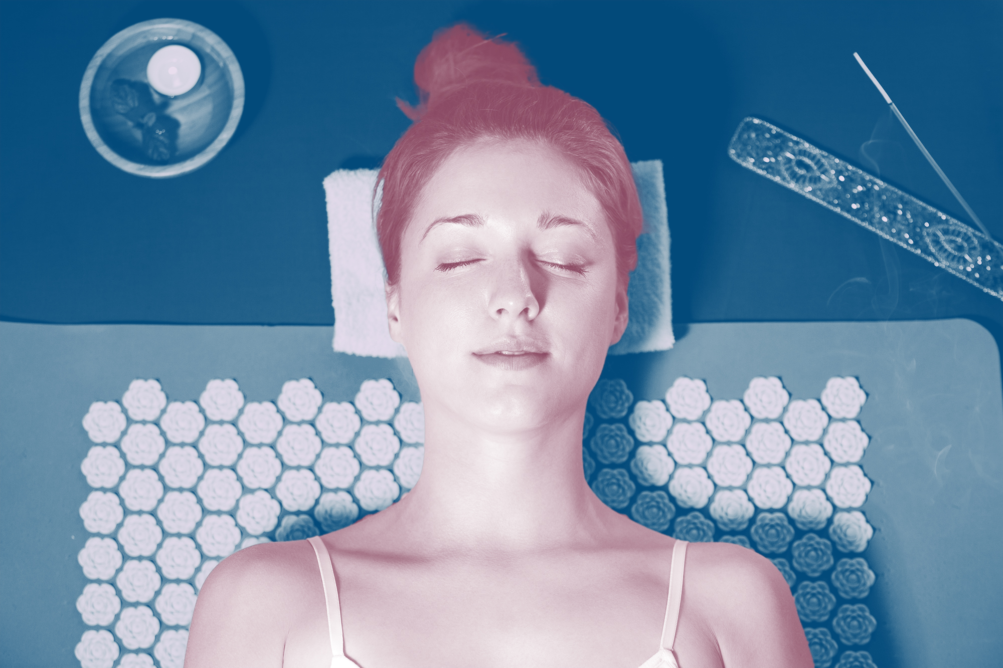 Woman with closed eyes Relaxing at home, lying on acupuncture mat