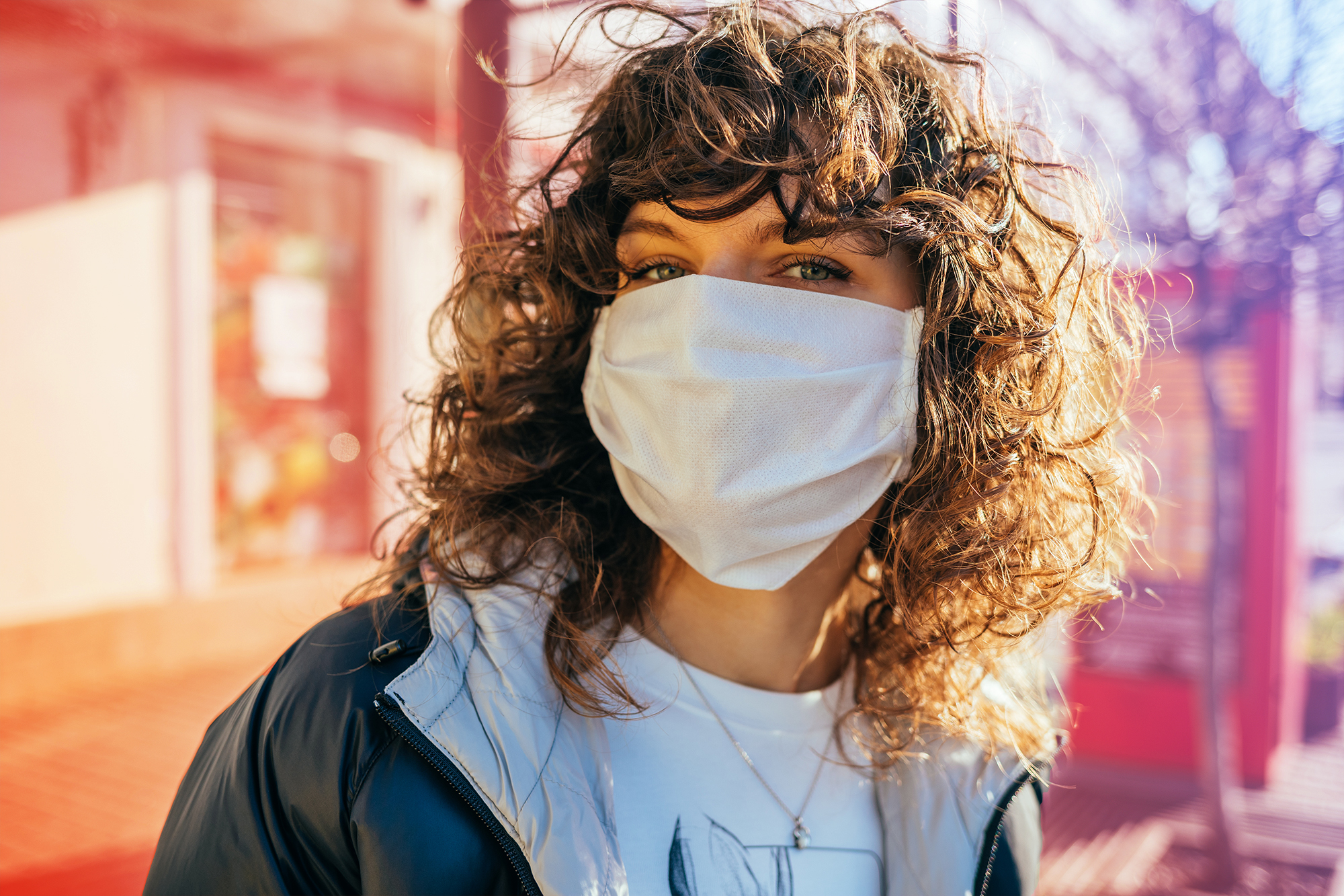 Prime Day Masks Deals , Portrait of young woman wearing medical facial mask standing outdoor in city on sunny spring day.
