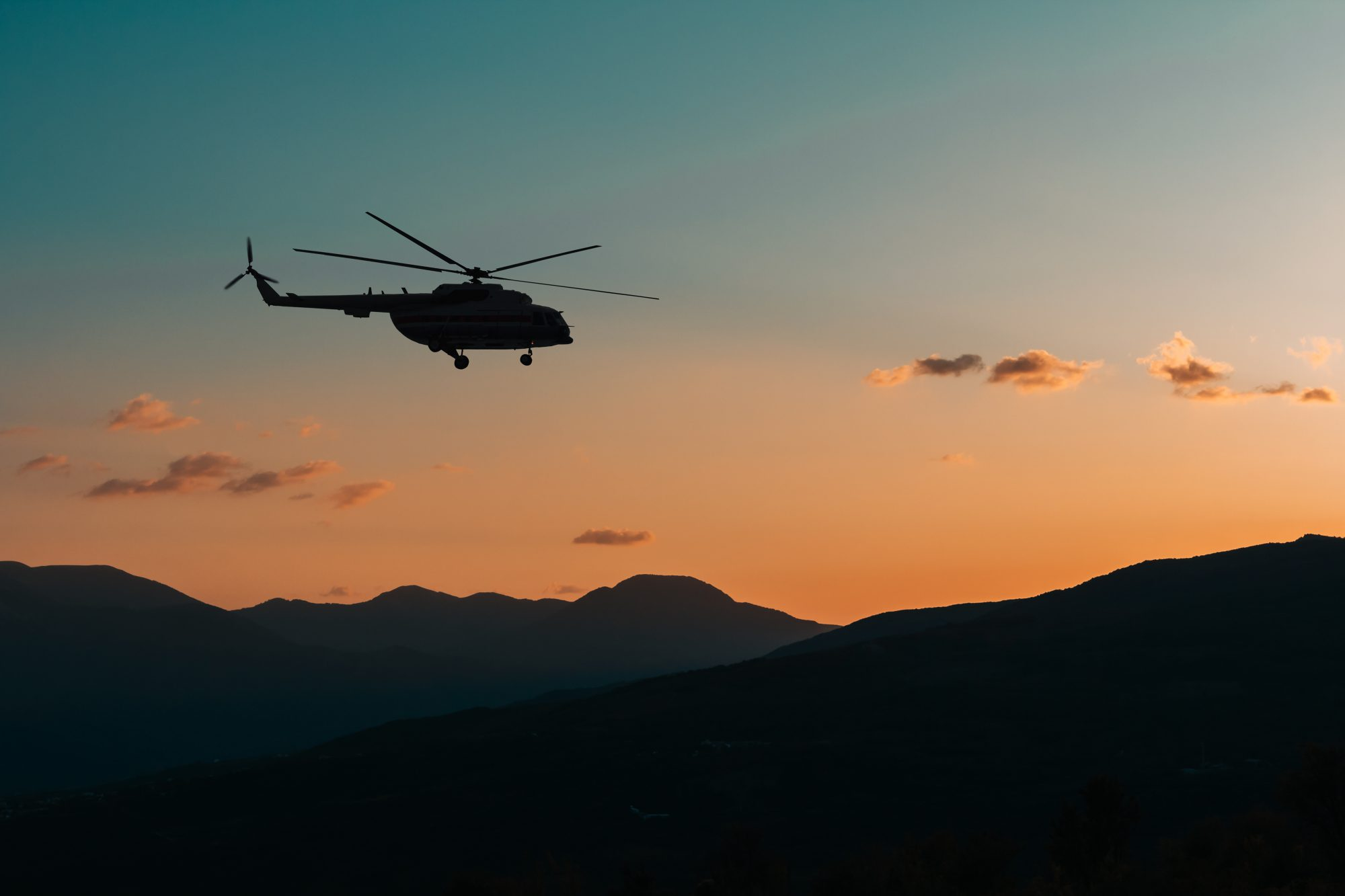 Helicopter flies in the mountains at sunset in the dark. Night rescue operation in a remote location, the search for missing people. Beautiful mountain landscape