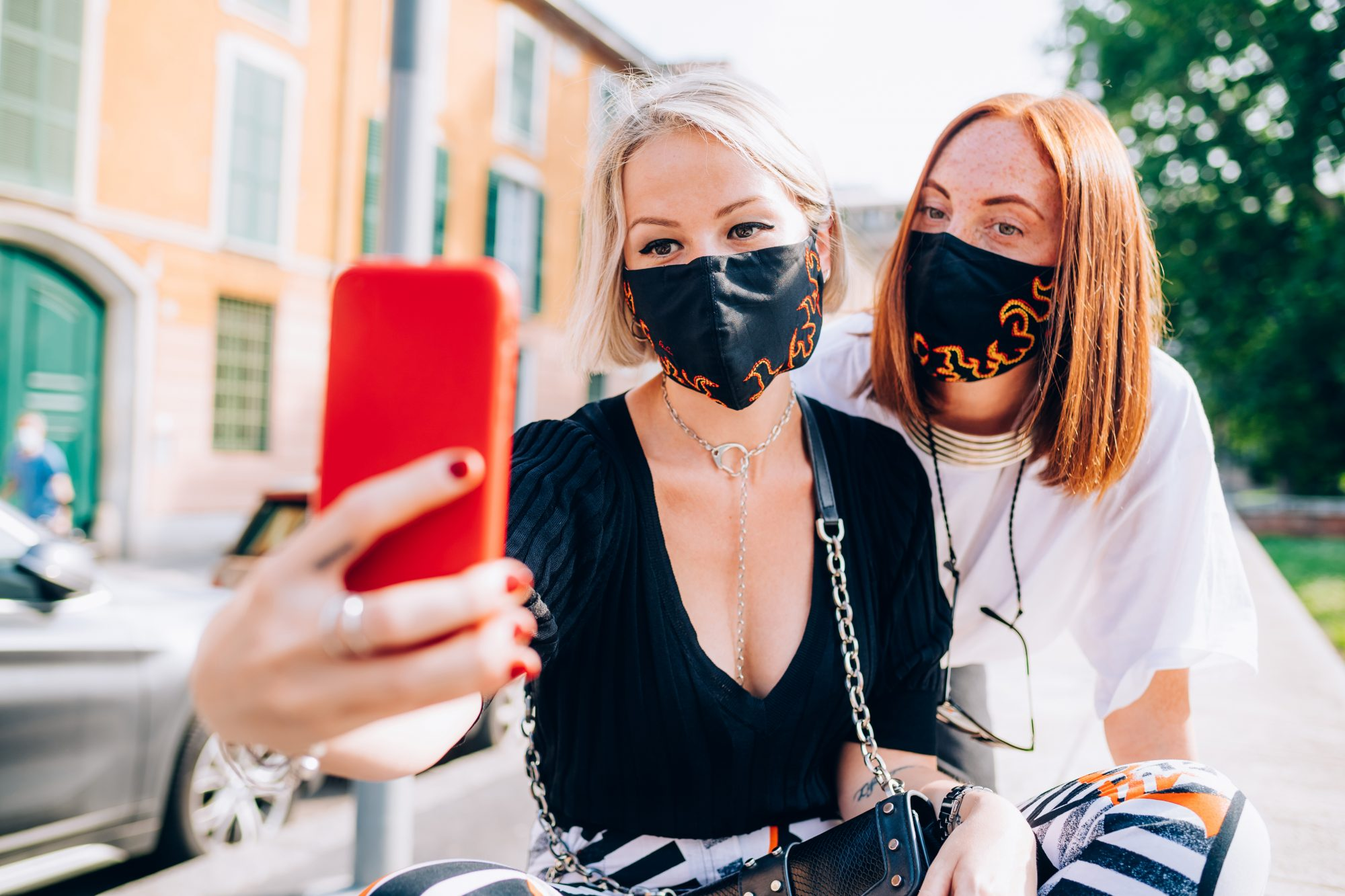 Two young women wearing face masks during Corona virus, sitting on a riverbank, taking selfie.The Best Black Friday Face Mask Deals